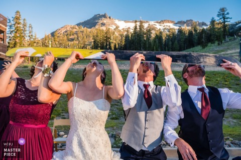 Bridal party shots off a ski together outside at the wedding reception at Lake Tahoe, California