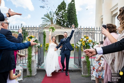 Sicilia bride and groom hold hands and celebrate with guests after the wedding ceremony