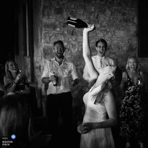 Bride enjoying her drinks at the wedding reception in Tenuta di Camposervoli, Siena, Italy