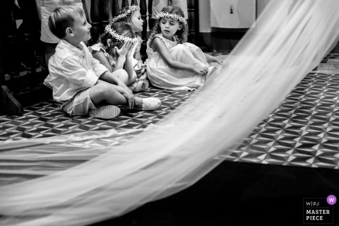 Rosario, Argentina kids sitting down next to the bride in her wedding dress before the wedding