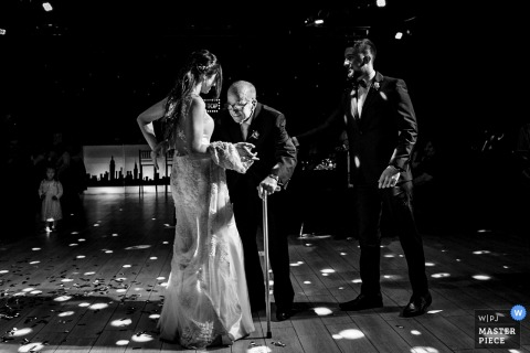 Groom helps brides father so that he can dance with her at the wedding reception in Rosario, Argentina