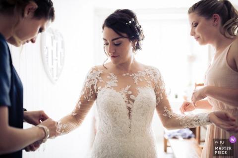 Photo de la mariée obtenant de l'aide pour sa robe avant la cérémonie de mariage au Locle, en Suisse