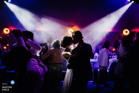 Purple ambience and dual spotlights illuminate the bride and groom as they dance in CRACH, FRANCE