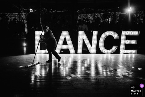 A vendor sweeps the dance floor in front of a large electric sign that reads: dance