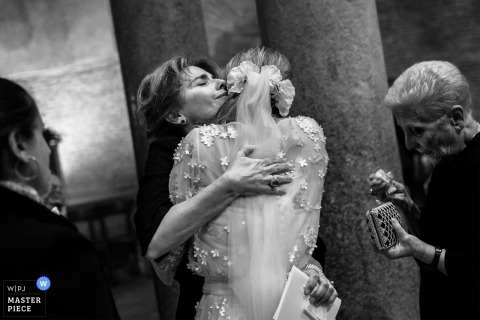 The bride's hugged by relative following her roma wedding ceremony