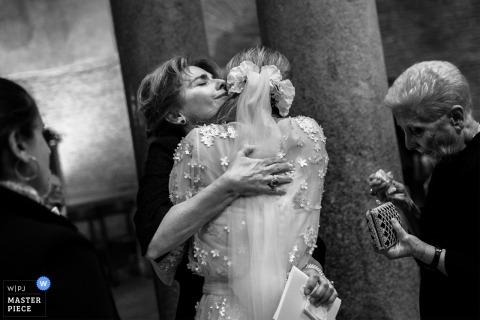 La mariée embrasse un membre de sa famille après la cérémonie de son mariage à Rome