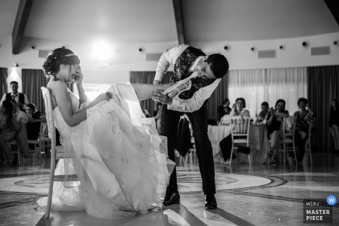 The groom retrieves the brides garter on the dance floor during there vibo valentia wedding reception