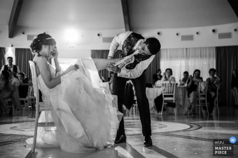 Der Bräutigam holt das Brautstrumpfband auf der Tanzfläche während des Hochzeitsempfangs ab