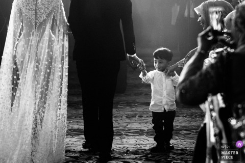 Bangkok groom holds the hand of a little boy while walking with the bride