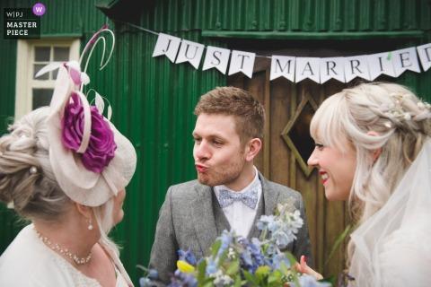 Braut und Bräutigam, die Spaß mit einem Gast nach der Hochzeitszeremonie im Avoncroft Museum, Birmingham lächeln und haben