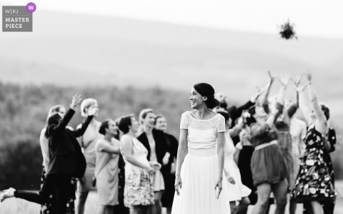 Outdoor photo of guests reaching for the bouquet in Luberon, France