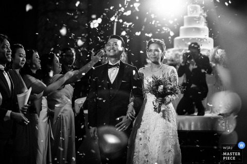 bride and groom smile as they walk in front of the wedding cake at the wedding reception in Bangkok