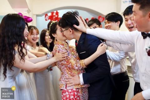 Porcelanowa impreza dla nowożeńców bawiąca się z panną młodą i panem młodym, gdy się całują