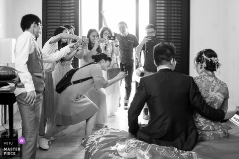China guests taking pictures of the bride and groom sitting next to each other