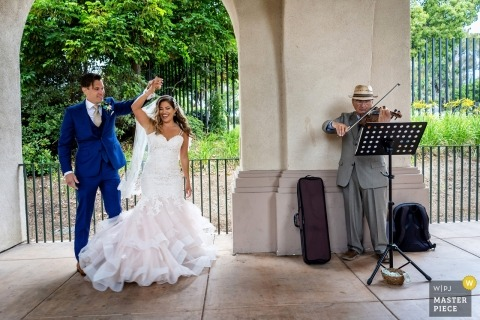Bride and groom dance next to the musician after the wedding ceremony in San Diego, California