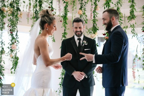 Photo of the bride and groom doing rock paper scissors during their indoor ceremony at Fishermen's Inn