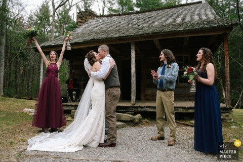 The bride and groom kiss following an outdoor wedding ceremony at the Great Smoky Mountains National Park, Cades Cove