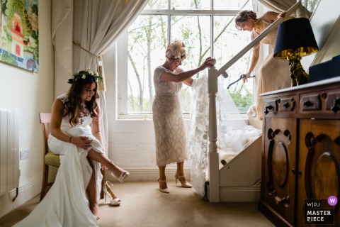 The bride put her shoes on as others help with getting ready preparations in this wedding day photo from Meath, Ireland