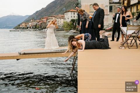 Aufnahmefoto von den Brautjungfern, die heraus über dem Wasser vom Dock für den Blumenstrauß erreichen, der gerade im Wasser von Comer See, Italien gelandet ist