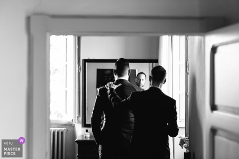The groom and best man prepare in the mirror for his Umbria, Tenuta Casa Bruciata wedding day