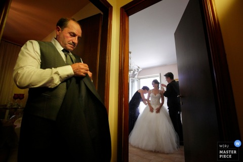 The brides father waits outside the room where she is preparing for her Reggio Calabria wedding