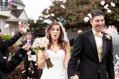 Panna młoda reaguje na płatki kwiatów w powietrzu, gdy wychodzi z ceremonii ze swoim nowym mężem w MacCallum House Inn, Mendocino, CA