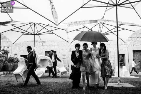 Schwarzweiss-Foto der Braut, die unter einem Meer von Regenschirmen im Regen in Oaxaca, Mexiko ankommt