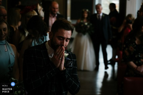 The groom wait in anticipation as his bride is being escorted down the aisle by her father during the RYE, England indoor wedding ceremony