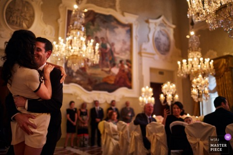 Elegant Tuscany wedding reception image of the bride and groom sharing in their first dance with guests seated under chandeliers