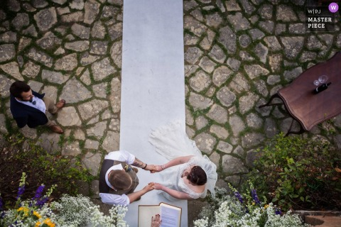 Birds eye view photo looking down on the bride and groom during the ceremony as they're holding hands