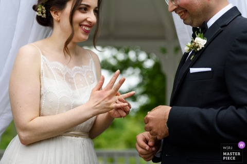 Outside photo of bride and groom smiling at each other during the wedding in Auberge des Gallant, Saint-Marthe, Quebec