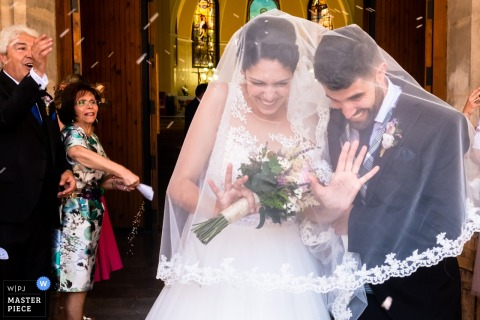 Outdoor photo of the bride and groom avoiding the rice being thrown at them after the wedding ceremony Alcoy