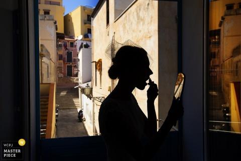 De foto van gesilhouetteerde bruid die haar krijgt maakt omhoog gedaan vóór de bruiloft Santa Flavia, Porticello, Palermo, Sicilië