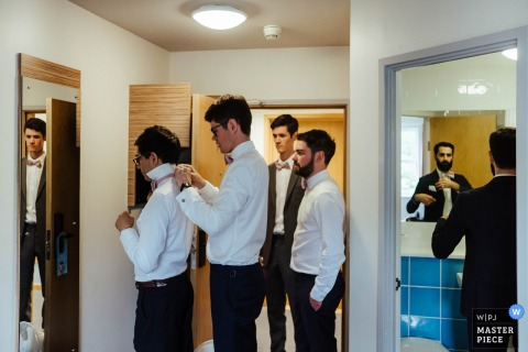 Groomsmen helping each other get ready before the wedding ceremony at the Barnston Lodge