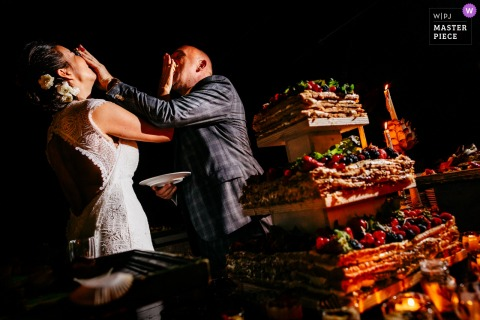 Italia wedding reception cake smashing photo with the bride and groom symmetrically captured