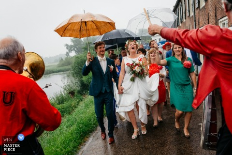 Acquoy wedding party March in the rainy streets with umbrellas and a marching band