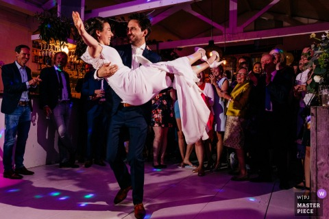 Den Haag wedding reception party Photo of the groom carrying the bride on the dance floor