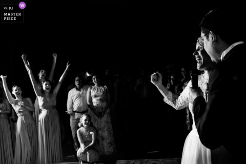 Black-and-white photo of wedding guests cheering during the bride and groom's first dance at this Mexico - Mexico-City party