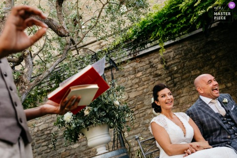 Ceremony Picture of the seated bride and groom laughing as the officiant speaks at this Italia wedding