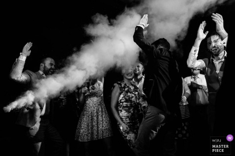 Black and white wedding image of the guests celebrating with the fog machine in Wijenburg