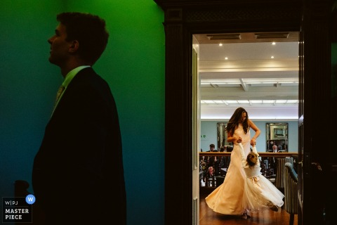 Color image of the groom profile and the bride full length in her dress in West Midlands, UK