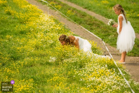 Image of the bride heading under an electric fence as the flower girl watches in Boerderij De Deel
