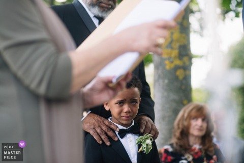 Photo of the ring bearer holding back tears during the outdoor ceremony in Ravello
