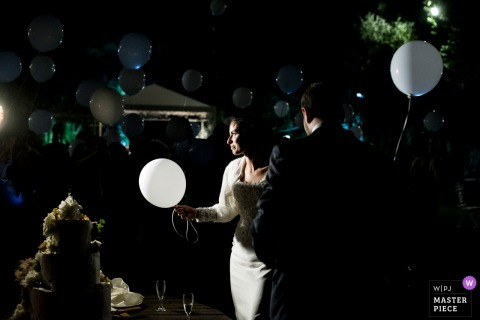 Outdoor photo of the bride and groom with balloons at the wedding reception in Tenuta del Polline, Rome