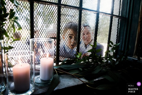 Photo of guests looking through a window at the wedding at Casale del Polline, Rome