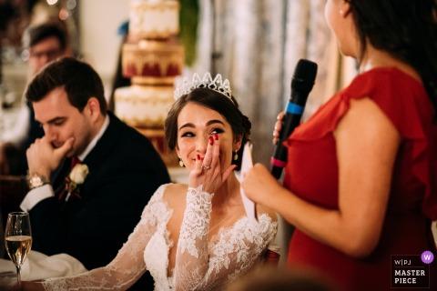 Foto der Braut emotional erhalten von der Trauzeuginrede am Hochzeitsempfang in der Dachgesimshalle, Großbritannien