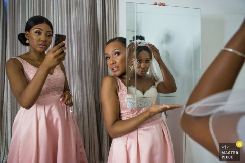 Picture of London bride looking in the mirror with the help of her bridesmaids