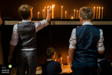 Little boys light the candles at the Serbian Orthodox Church wedding ceremony in London