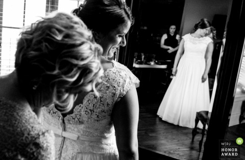 North Carolina wedding photographer - Bride smiles as she gets her dress on at the Childress Vineyards