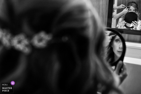 La sposa si guarda allo specchio mentre i suoi capelli vengono fatti prima della cerimonia di nozze a South Lake Tahoe, Nevada